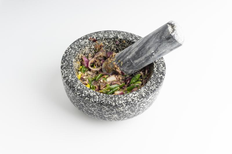 A mortar and pestle Lesung Batu. With mixed crushed chilies, shallots and anchovies on white background. Selective focus and crop fragment royalty free stock image