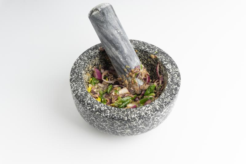 A mortar and pestle Lesung Batu. With mixed crushed chilies, shallots and anchovies on white background. Selective focus and crop fragment stock image