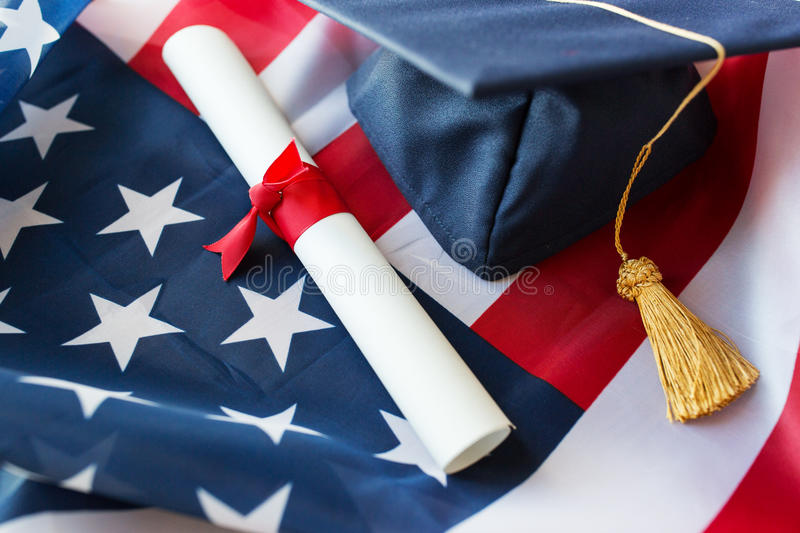 Mortarboard and diploma on american flag. Education, graduation, patriotism and nationalism concept - close up of bachelor hat and diploma on american flag royalty free stock images
