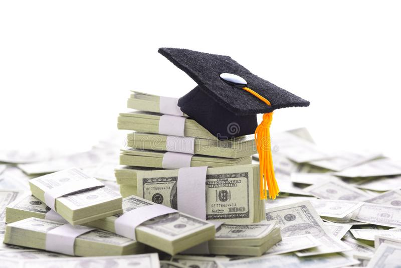 Mortarboard on a pile of money representing the high cost of higher education and bribery royalty free stock photography