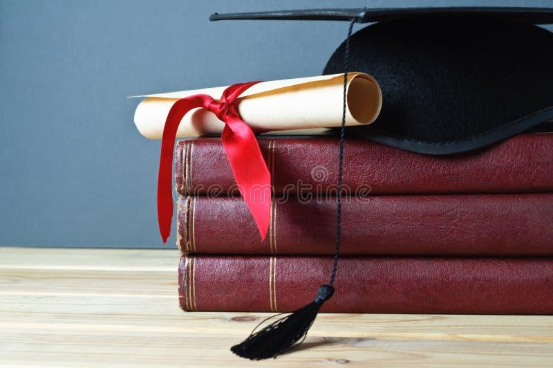 Mortarboard, rolo e livros da graduação fotos de stock royalty free