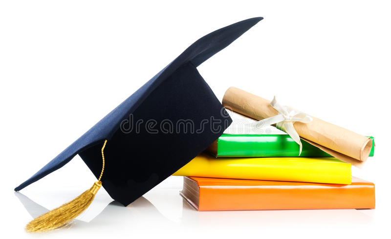 Mortarboard and vintage graduation scroll, tied with red ribbon. On a stack of books stock photography