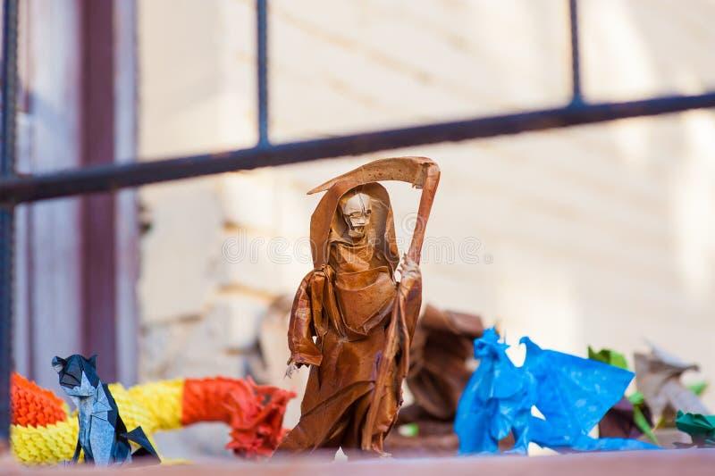 Morte con una carta della falce, donna anziana di origami con una falce immagine stock