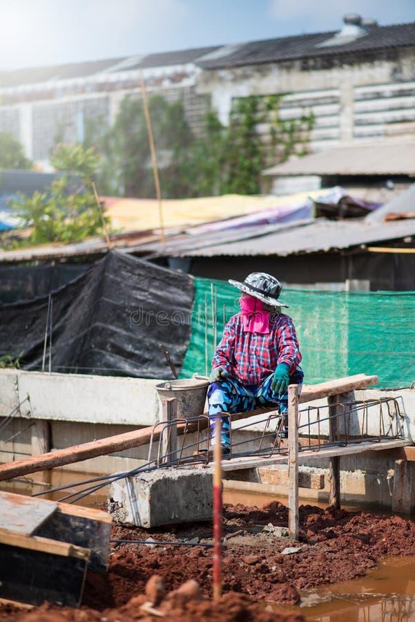 Mortel för stuckatör för kvinnabyggnadsarbetare väntande på på cementet, Bangkok Thailand 10 februari 18 arkivfoto