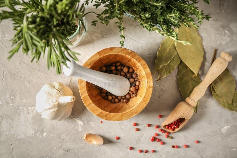 Mortel med mortelstöten, kryddor och örter på tabellen, bästa sikt royaltyfria foton