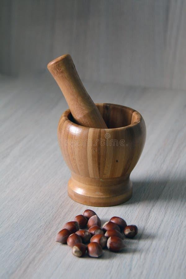Mortel och en mortelstöt med hasselnötter arkivbild