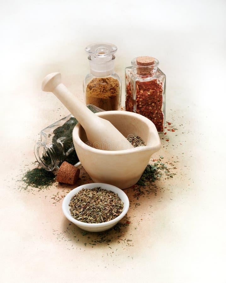 Mortel och mortelstöt med kryddor och örter på den vita kanfastabelltorkduken arkivbild
