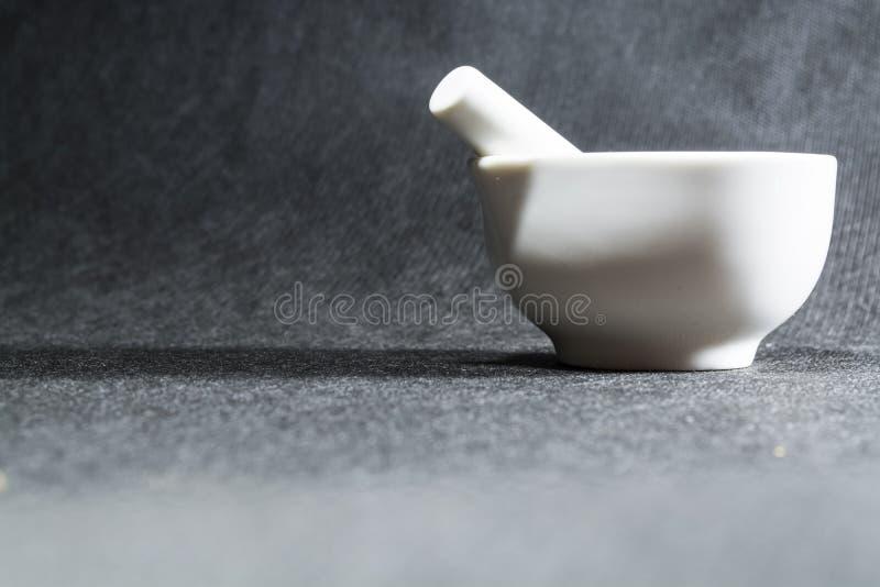Mortero blanco con una maja de la porcelana Un cuenco de consumición para machacar de especias Fondo negro Utensilios de la cocin foto de archivo