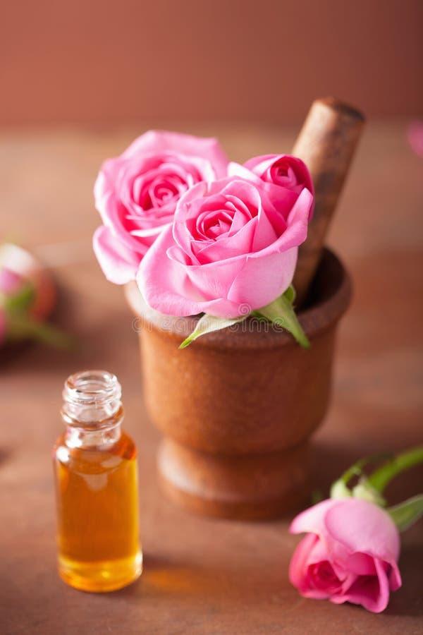 Mortero con las flores color de rosa y el aceite esencial para el aromatherapy y imagen de archivo libre de regalías