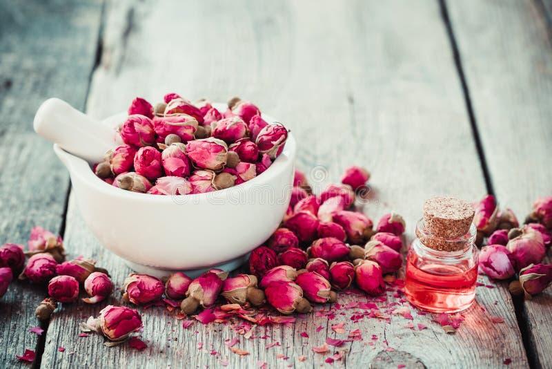 Mortero con los brotes color de rosa y el aceite de rosas esencial foto de archivo libre de regalías