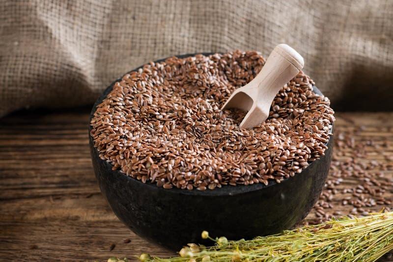 Mortero de mármol negro por completo de las semillas de lino imagen de archivo libre de regalías