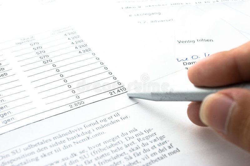 Mortgage. Man checking Mortgage papers with silver pen royalty free stock image