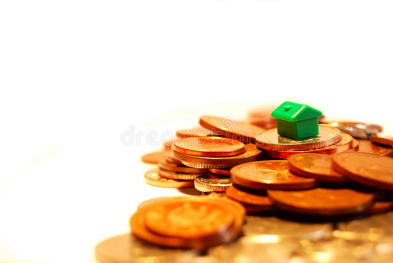 Mortgage. Small green house representing a mortgage surrounded by United Kingdom change currency royalty free stock photography
