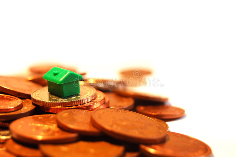 Mortgage. Small green house representing a mortgage surrounded by United Kingdom change currency royalty free stock photos