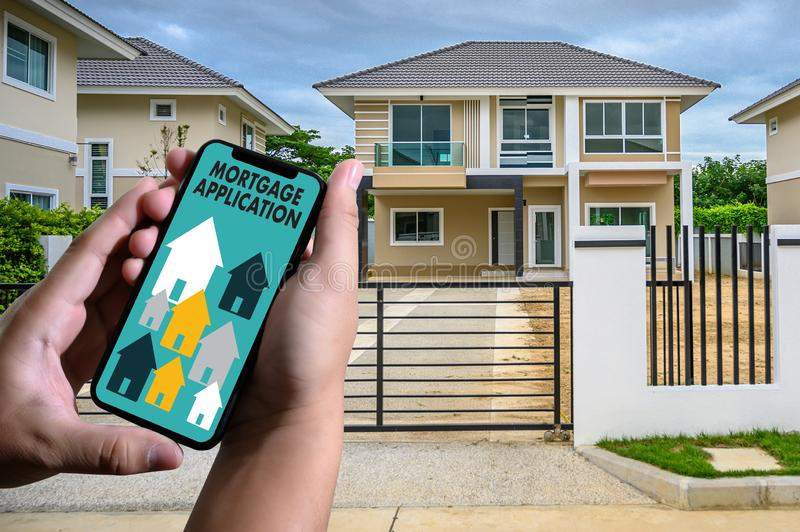 MORTGAGE APPLICATION CONCEPT man hand use phone in front of their new home stock photo