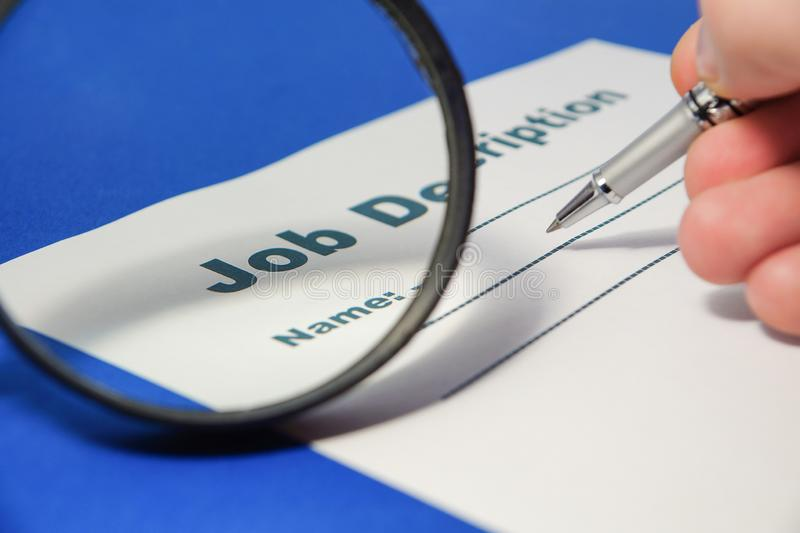 Job Description with Pen and Hand on blue background. Job Description with Hand and Pen on blue background close up stock photo