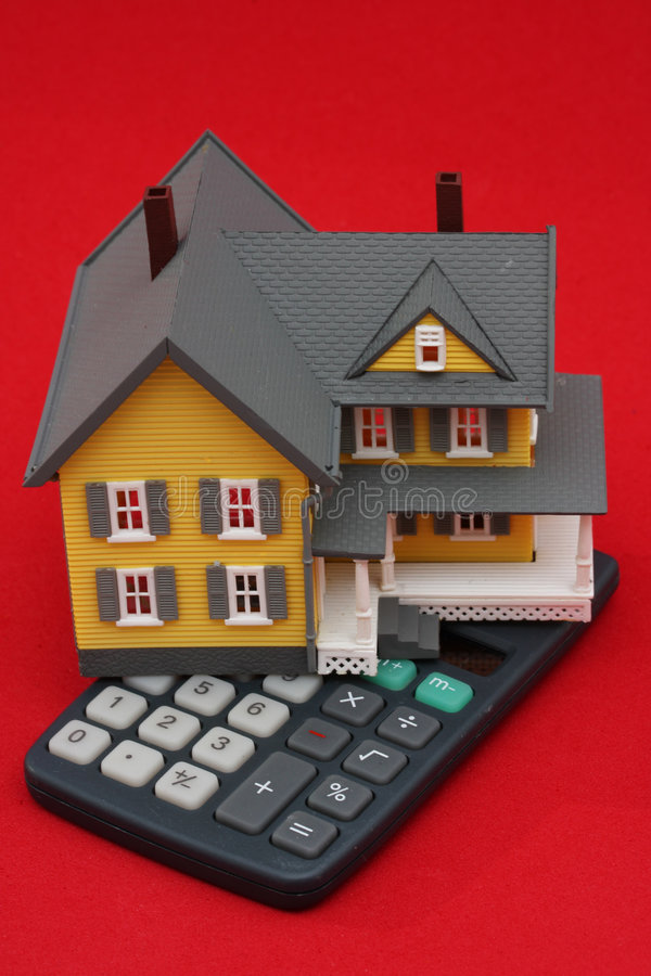 Mortgage Calculator. Yellow house on a calculator, red background royalty free stock images