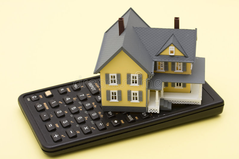 Mortgage Calculator. Model house sitting on calculator on a yellow background royalty free stock images
