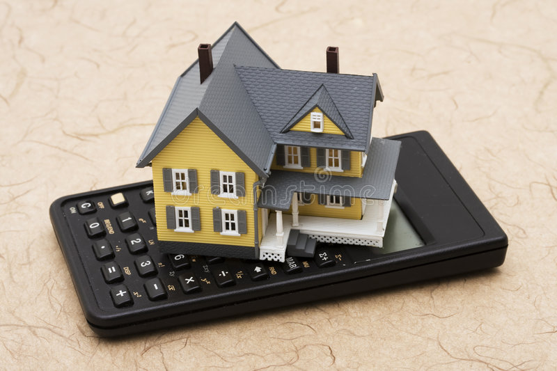 Mortgage Calculator. Model house sitting on calculator, mortgage costs royalty free stock photography