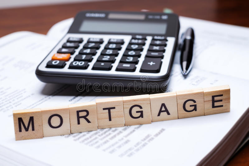 Mortgage. Calculator with the word Mortgage written in wooden block letters royalty free stock photos