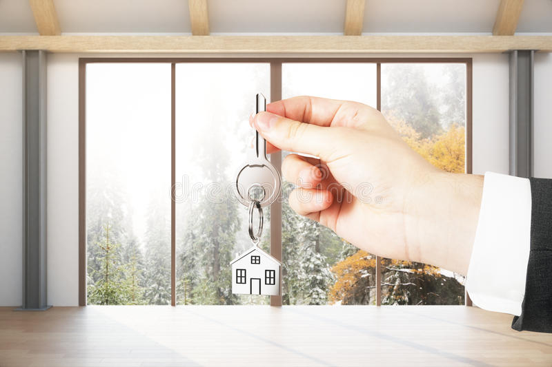 Mortgage concept. Close up of hand with key in modern interior with panoramic landscape view. Mortgage concept royalty free stock photo