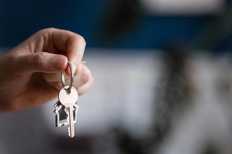 Mortgage concept. Men hand holding key with house shaped keychain. Modern light lobby interior. Real estate, moving home. House key and keychain in the form of stock photo