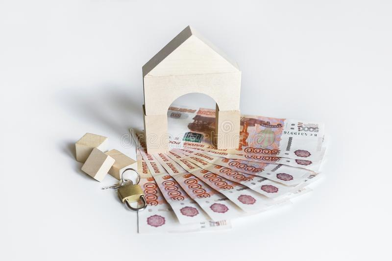 Mortgage concept. Property investment concept. House made of wooden bricks and padlock and key on a pile of Russian banknotes stock photo