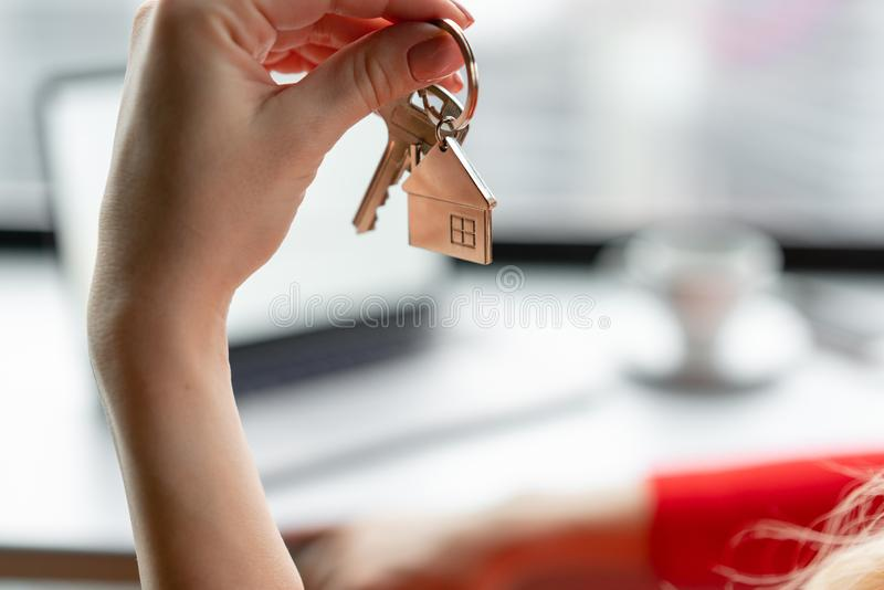 Mortgage concept. Woman in red coral business suit holding key with house shaped keychain. Modern light lobby interior royalty free stock photo