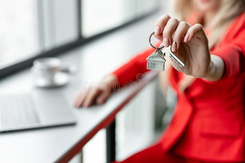 Mortgage concept. Woman in red coral business suit holding key with house shaped keychain. Modern light lobby interior stock images