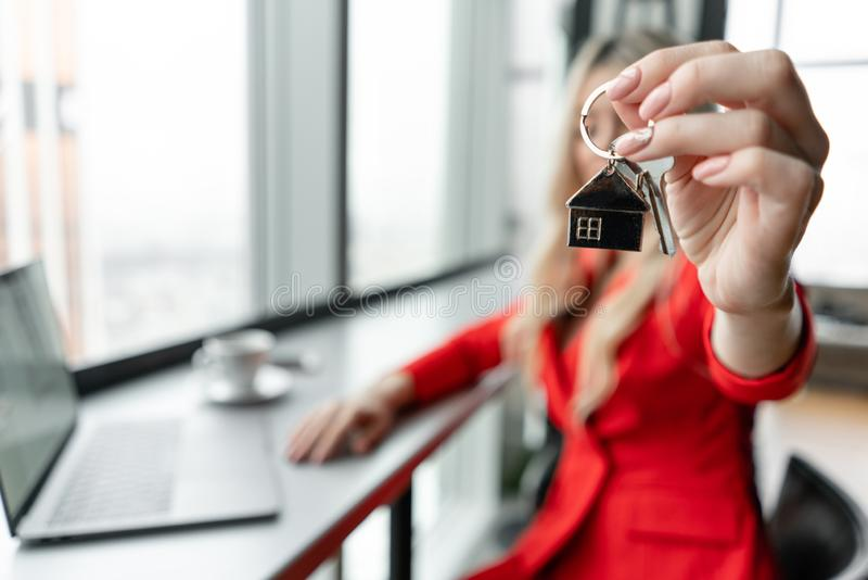 Mortgage concept. Woman in red coral business suit holding key with house shaped keychain. Modern light lobby interior royalty free stock images
