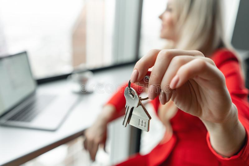 Mortgage concept. Woman in red coral business suit holding key with house shaped keychain. Modern light lobby interior royalty free stock image