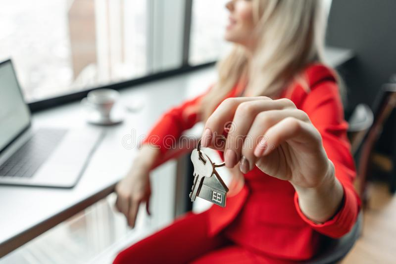 Mortgage concept. Woman in red coral business suit holding key with house shaped keychain. Modern light lobby interior stock photo