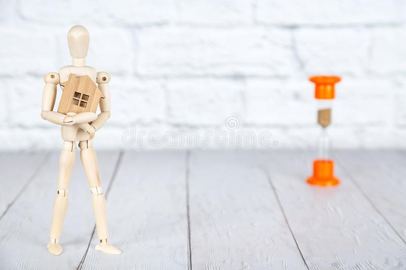 Mortgage concept. Wooden human puppet holding a house figure and hourglass beside. Mortgage concept. Wooden human puppet holding a house figure and an hourglass royalty free stock photography