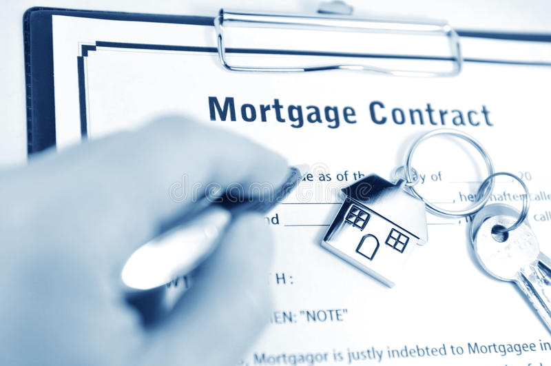 Mortgage contract. Signing the mortgage contract with keys and symbolic house keyring stock photography