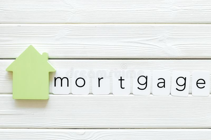 Mortgage copy for credit concept with house toy on white wooden background top view space for text. Purchasing a new property on credit. Mortgage copy for credit royalty free stock photos