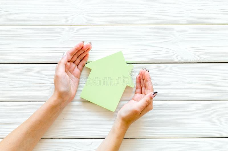 Mortgage credit concept with house toy in hands on white wooden background top view space for text stock photo