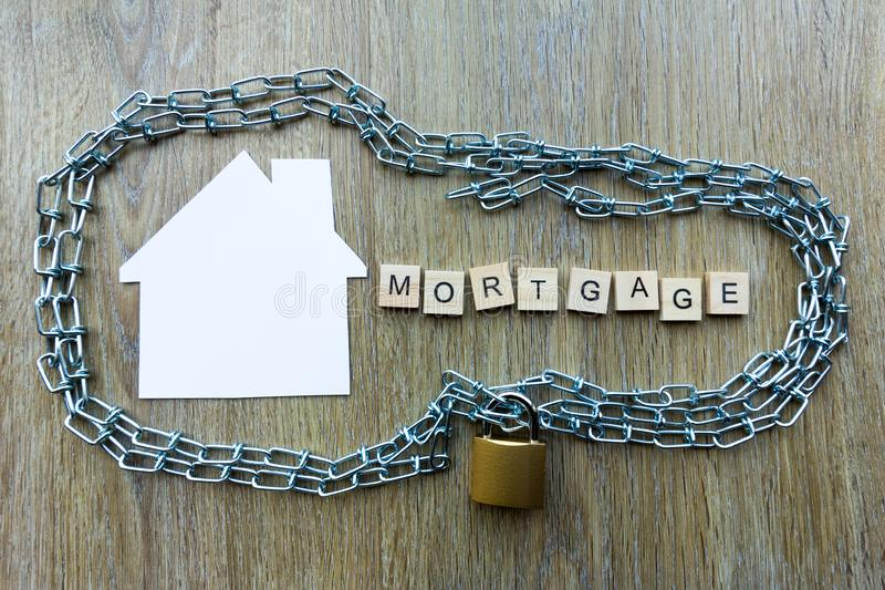 Chain surrounding a house with the word mortgage. Mortgage debt concept - chain surrounding a house with the word mortgage royalty free stock images