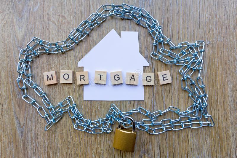 Chain surrounding a house with the word mortgage. Mortgage debt concept - chain surrounding a house with the word mortgage royalty free stock photo