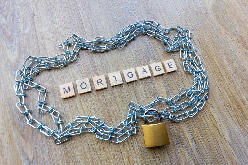 Chain surrounding a house with the word mortgage. Mortgage debt concept - chain surrounding a house with the word mortgage royalty free stock photos