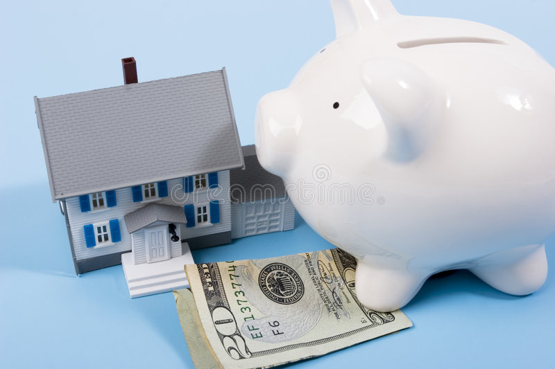 Mortgage and down payment. Two-story house with twenty dollar bill and a piggy bank royalty free stock photo