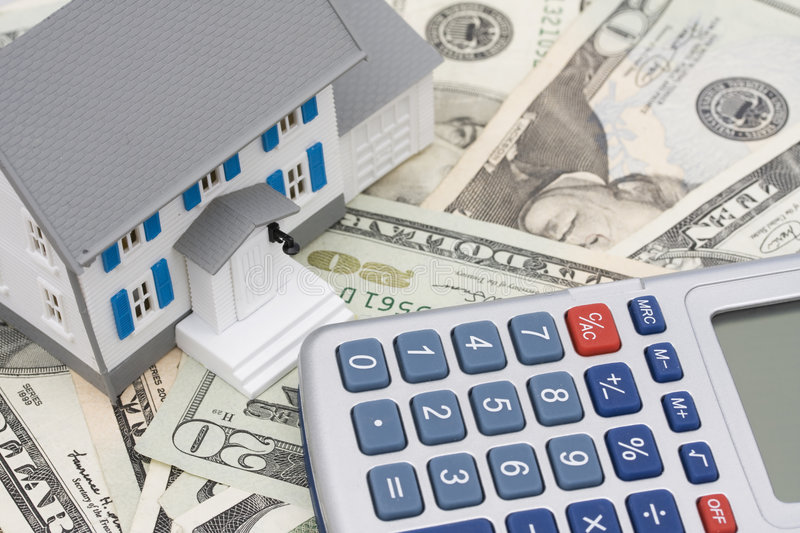 Mortgage and Down Payment. House sitting on American currency and calculator stock photo