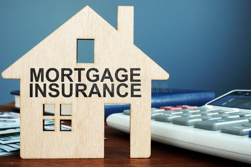 Mortgage insurance. Wooden home, money and calculator stock photo