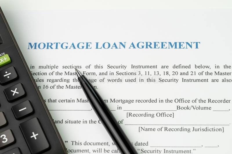 Mortgage loan agreement sign contract concept, pen with calculator on mortgage form or contract, long term debt or real estate in. Vestment royalty free stock image