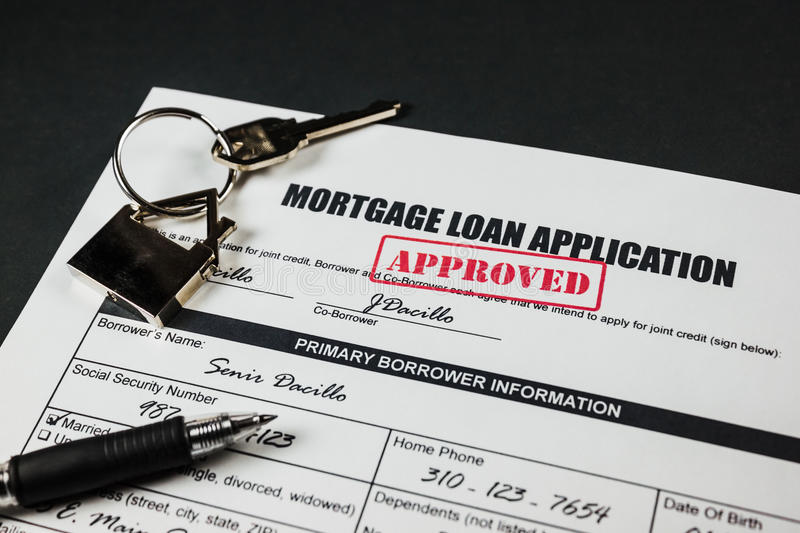 Mortgage Loan Application Approved 003. Filled-up mortgage loan application form with approved stamp, black pen, key and a house keychain royalty free stock image