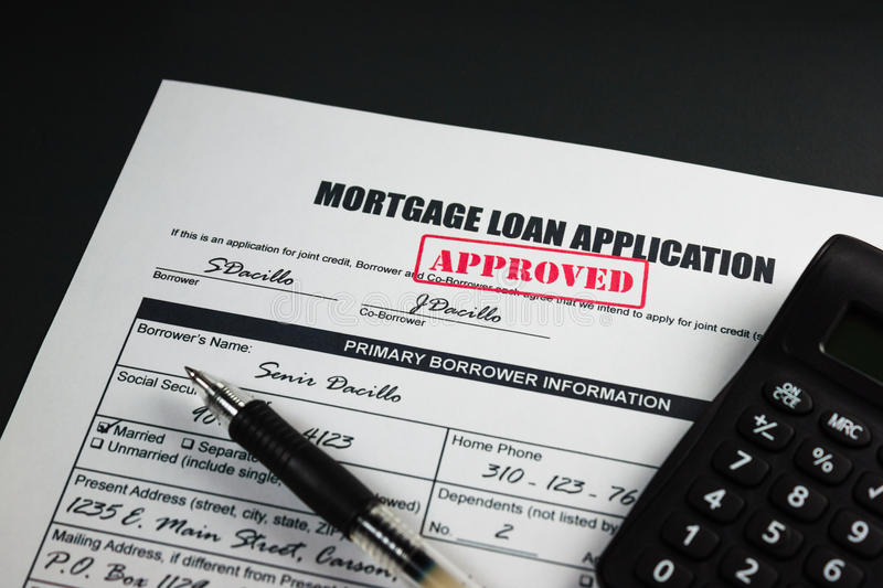 Mortgage Loan Application Approved 001. Filled-up mortgage loan application form with approved stamp, calculator and a black pen royalty free stock photos