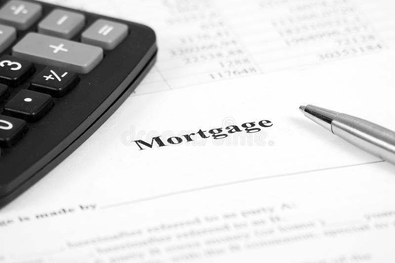 Mortgage loan commitment document. A pen and calculator sitting on a mortgage loan commitment document stock photography