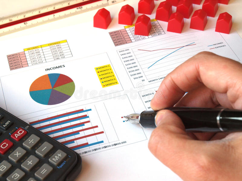 Mortgage loan. Concept: toy houses and financial graphs, hand and pen, calculator machine stock image