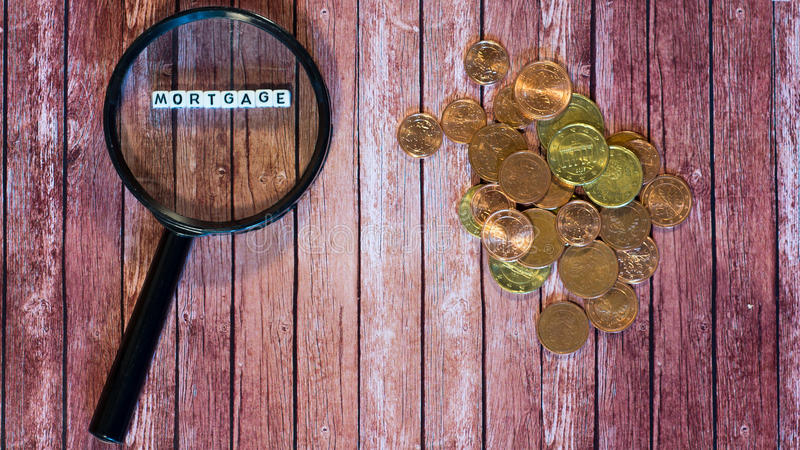 Mortgage loan, magnifying glass and coins stock photos