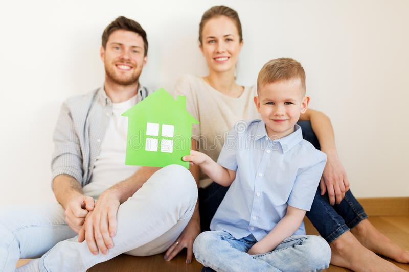 Happy family with green house moving to new home. Mortgage, people, housing and real estate concept - happy family with green paper house moving to new home stock photography