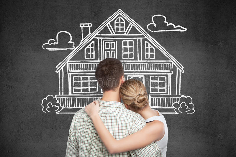 Mortgage and property concept. Back view of young couple looking at house sketch on dark concrete background. Mortgage and property concept